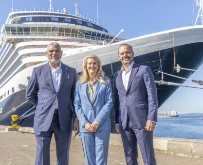 Executives from Holland America Line in front of Nieuw Amsterdam in the Port of Seattle.