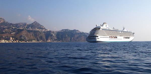 Crystal Serenity, at anchor Friday Aug. 28, 2009 in Naxos, Sicily. The extremely popular tourist town of Taormina appears high-atop the cliffs to the left in this image. Photo by Michael Coleman